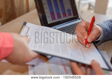 Close up of male hand putting signature in the contract entering into the new contract written statement declaring the price. Business partnership concept