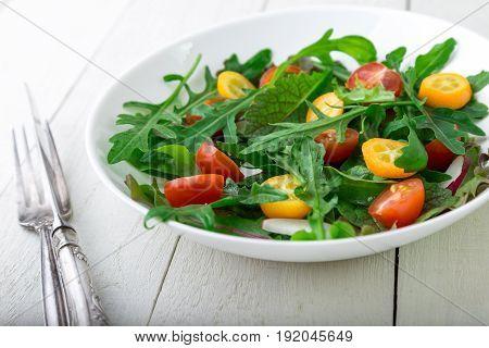 Fresh Arugula Salad With Kumquat And Tomato Cherry On White Wooden Background. Close Up. Healthy Foo