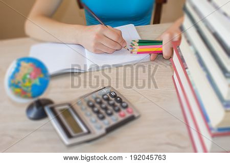 Girl doing lessons at home. Education concept - books on the desk in the auditorium. Girl studying