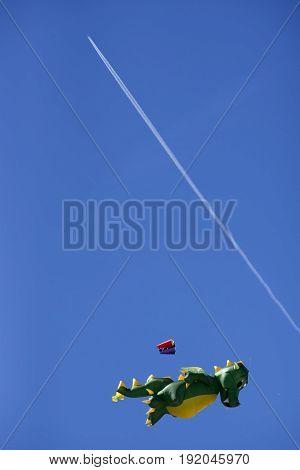 FANOE DENMARK JUNE 17 2017: Kite high up and jet vapor in the blue sky over Fanoe beach. Fanoe Kite Fliers Meeting June 2017.