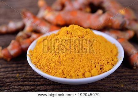 turmeric powder in white bowl and raw turmeric on wooden table