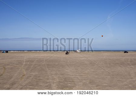 FANOE DENMARK JUNE 17 2017: A man with straw hat and a kite on the bike and the North Sea in the background on Fanoe beach. Fanoe Kite Fliers Meeting June 2017.