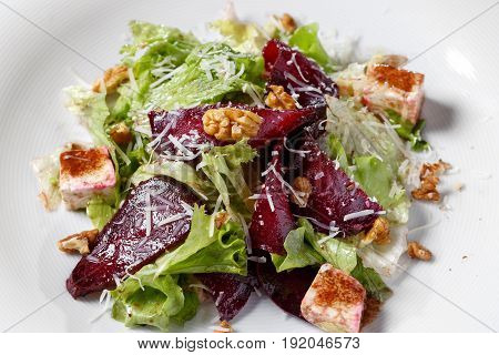 Beautiful Spring Salad with Beet and Pear, Close-up. kale lettuce, nuts, feta cheese. on a white plate, the dish is served in the restaurant