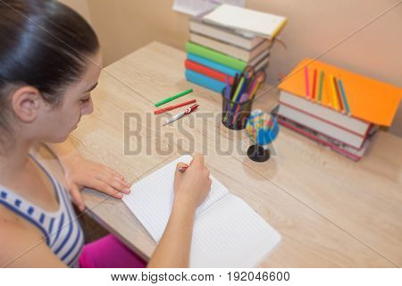 Student Young Girl write in notebook between books. Education concept - books on the desk