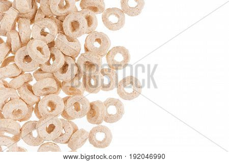 Decorative border of beige rings corn flakes isolated with copy space. Cereals background.