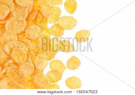 Decorative border of golden corn flakes isolated with copy space. Cereals texture.