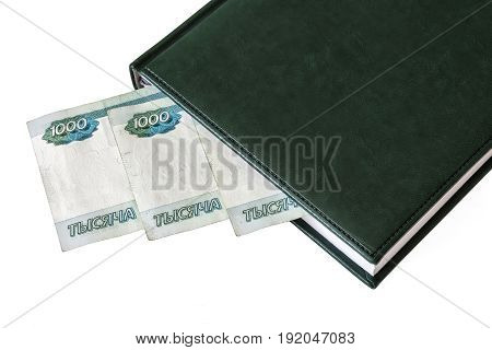 Between the sheets of the closed diary one can see a part of the denominations of 1000 Russian rubles