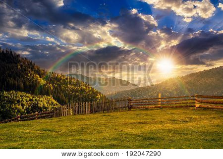 Fence Through The Grassy Meadow In Mountains At Sunset With Rainbow