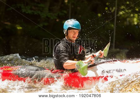 Bala Wales UK - June 18 2017: White water kayaker shooting the rapids at the National White Water Centre on the River Tryweryn in Snowdonia National Park