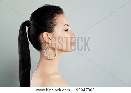Pretty Woman with Earrings. Profile on gray background