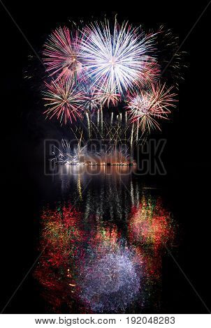 Firework. Beautiful colorful fireworks on the water surface with a clean black background. Fun festival and contest of Firefighters Brno Dam - Czech Republic.