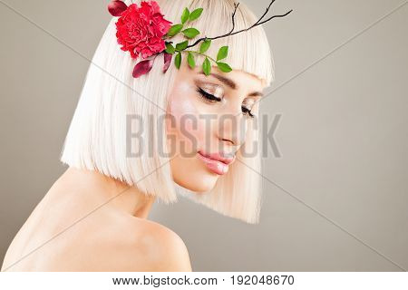 Glamorous Blonde Model Woman with Makeup Bob Hairstyle and Flowers. Facial Treatment and Cosmetology