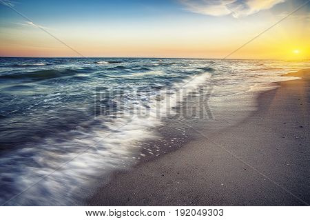 Sea surf wave photographed with long exposure. dramatic tropical sea and sky sunset