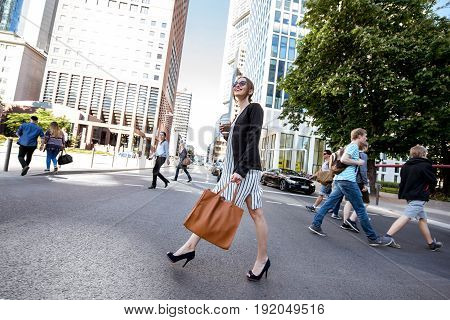 FRANKFURT AM MAIN, GERMANY - May 16, 2017: Business people crossing the Taunustor street at the modern district in Frankfurt city.