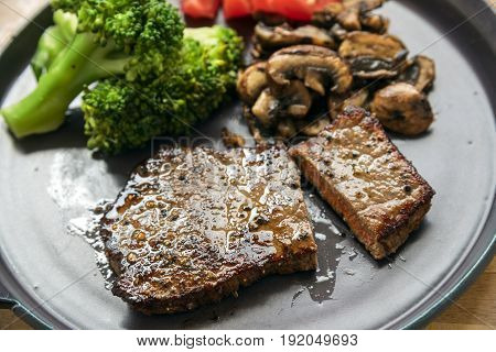 beef steak with vegetables like broccoli champignons and tomatoes low carb diet dinner on a gray plate selected focus narrow depth of field