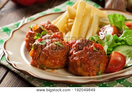 Roasted Meatballs In Tomato Sauce With French Fries And Salad