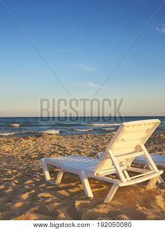 Deckchairs on the sandy beaches for tourists to sit and relax with soft ocean waves breaking on beach