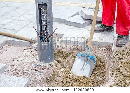Worker is leveling gravel with shovel around the base of the electric metal lamppost by removing excess material.