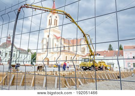 View on the pump crane for lifting and casting concrete at construction site through a fence wire with quadratic shape.