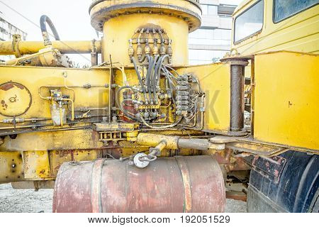 Hydraulic pressure pipes and connection fittings levers valves on control panel of industrial system on construction machinery.