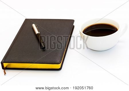 Pen On The Black Day Planner And A Cup Of Black Coffee On A White Background. Minimal Business Conce