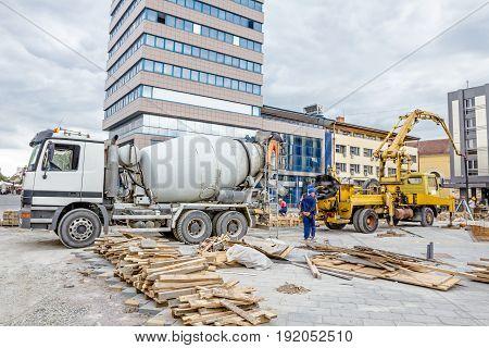 Truck mixer is pouring concrete into concrete pump for casting.
