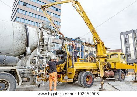 Truck mixer is pouring concrete into concrete pump for casting.