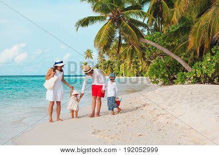 happy family with two kids walking on tropical beach