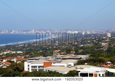 Above view of commercial and residential buildings urban coastal landscape against blue Durban city skyline in South Africa