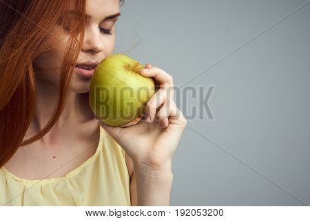 Diet, nutrition, apple, woman with apple, woman on gray background.