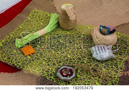 Sewing textile or cloth. Gold scissors pin cushion, and natural white fabric. Work table of a tailor. Shallow depth of field, Focus on scissors.