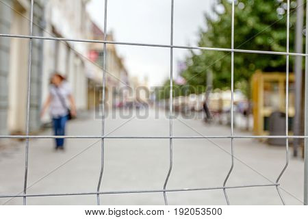 View through a fence wire with quadratic shape on the business people passing by in the city street.