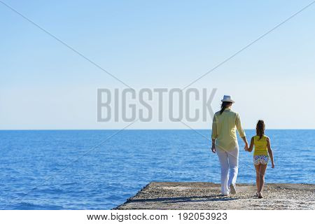 European Pregnant Mom And Her Little Daughter Are Walking On Breakwater To The Blue Sea Under Clear