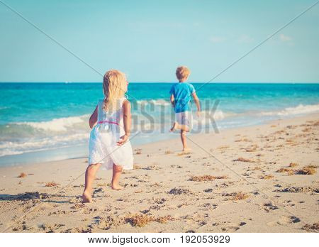 little boy and girl running on beach, family beach holiday