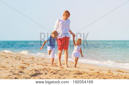 father with little son and daugther walking on beach