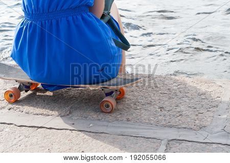 The Girl Has A Rest, Sitting On A Skateboard