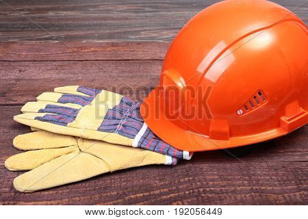 Orange hard hat and gloves for work on wood background