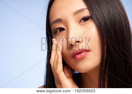 Woman with cream on face, face care, woman on blue background portrait.