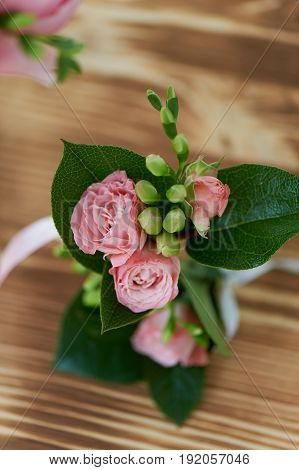 Wedding boutonniere for the groom.A wedding decoration. The greenery and small pink flower