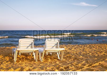 Two deckchairs on the sandy beaches for tourists to sit and relax with soft ocean waves breaking on beach