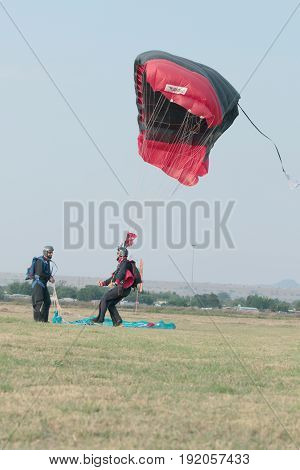 Skydiver Landing Next To Another With Open Parachute.