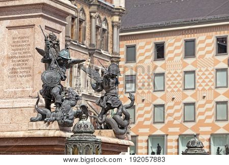 statue at corner of the Marian column pedestal on the central square Marienplatz in Munich Germany