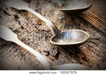 Old silver spoon that is dark from corrosion on wooden background .