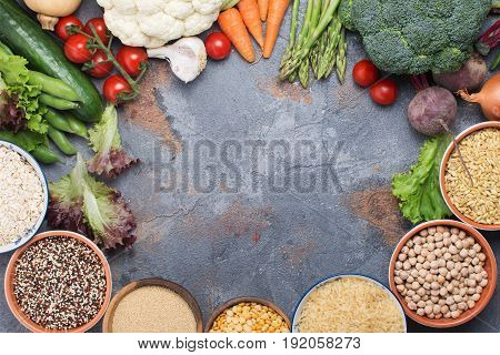 Grains in a bowl and vegetables arranged in a circle with copy space in the middle, broccoli, squash, beans, tomatoes, carrots, avocado, quinoa, peas, rice, oats, selective focus