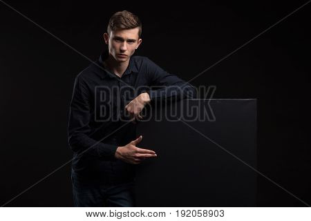 Young man portrait of a confident businessman showing presentation, pointing paper placard black background. Ideal for banners, registration forms, presentation, landings, presenting concept.