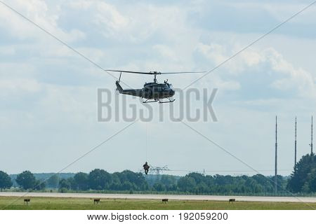 BERLIN GERMANY - JUNE 02 2016: Demonstration flight of military helicopter Bell UH-1 Iroquois with the landing operation. German Army. Exhibition ILA Berlin Air Show 2016