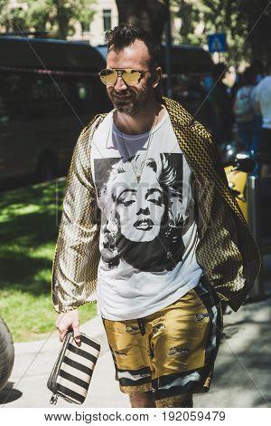 MILAN ITALY - JUNE 19: Fashionable man poses outside Armani fashion show building during Milan Men's Fashion Week on JUNE 19 2017 in Milan.
