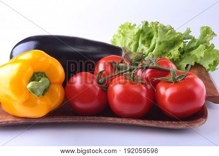 Fresh assorted vegetables, eggplant, bell pepper, tomato, garlic with leaf lettuce. Isolated on white background. Selective focus