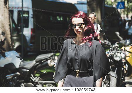 MILAN ITALY - JUNE 19: Fashionable woman poses outside Armani fashion show building during Milan Men's Fashion Week on JUNE 19 2017 in Milan.
