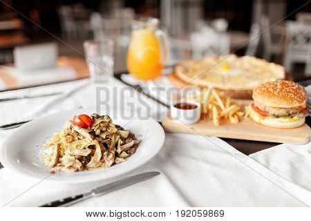 beautiful table of italian pasta, pizza, burger and drinks. hearty lunch in the afternoon. focus on the pasta.
